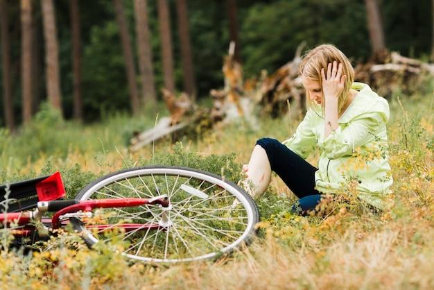 Frau, die auf dem boden mit einer verletzung sitzt