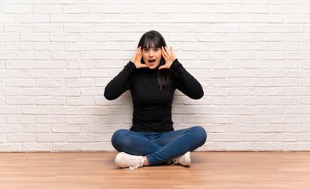Frau, die auf dem boden mit überraschungsausdruck sitzt