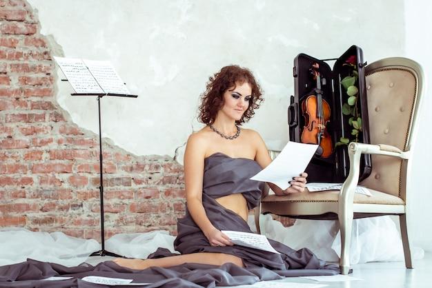 Frau, die auf dem boden nahe dem stuhl mit violine sitzt