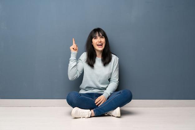 Frau, die auf dem boden sitzt, der beabsichtigt, die lösung beim anheben eines fingers zu verwirklichen