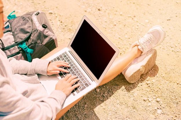Frau, die auf dem boden sitzt und im laptop arbeitet