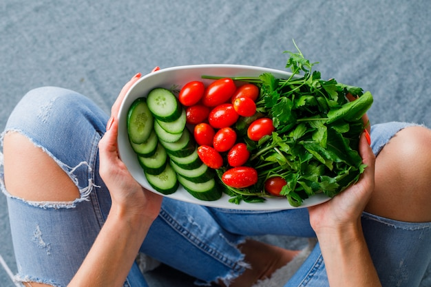 Frau, die auf dem boden sitzt und salat auf grauer oberfläche, draufsicht hält