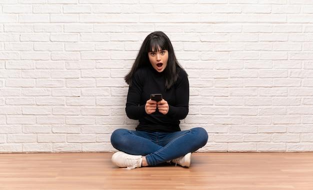 Frau, die auf dem boden überrascht sitzt und eine mitteilung sendet