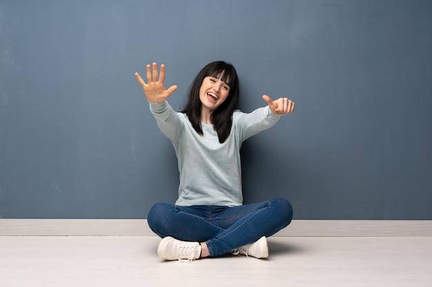 Frau, die auf dem boden zählt sechs mit den fingern sitzt