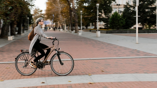 Frau, die auf dem fahrrad long shot steht