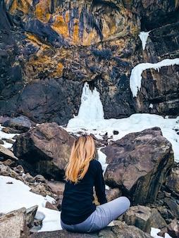 Frau, die auf dem felsenberg sitzt