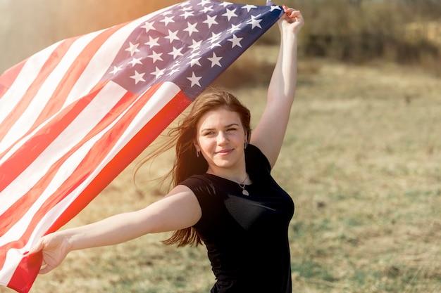 Frau, die auf dem gebiet steht und amerikanische flagge hält
