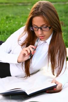 Frau, die auf dem gras liegt und ein buch liest