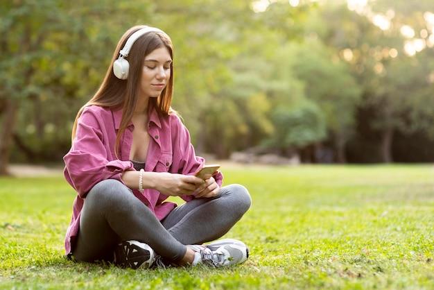 Frau, die auf dem gras sitzt und ihr telefon überprüft
