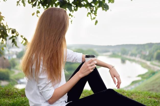 Frau, die auf dem gras stationiert, die ansicht des flusses sich entspannt und genießt