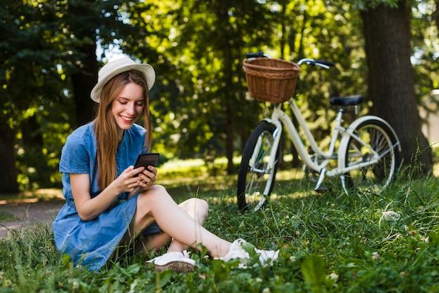 Frau, die auf dem gras überprüft ihr telefon sitzt