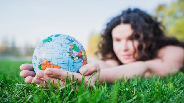 Frau, die auf dem grünen gras hält kugel in der hand über grünem gras liegt