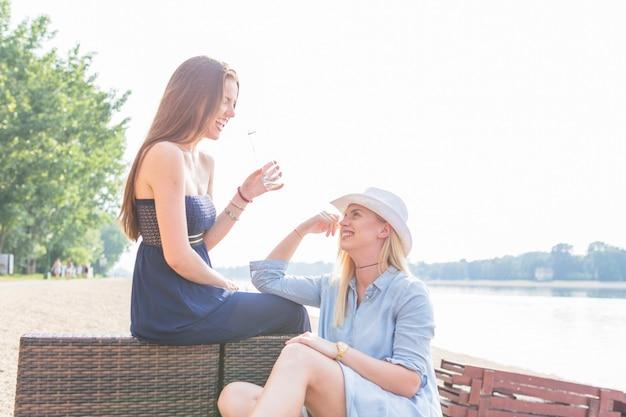 Frau, die auf dem klubsessel betrachtet ihre freunde halten wasserflasche am strand sitzt