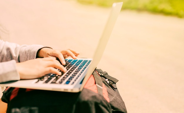 Frau, die auf dem laptop gesetzt auf rucksäcke schreibt