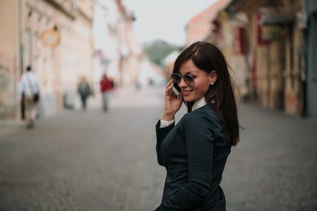 Frau, die auf dem mobile bei der erforschung der stadt spricht