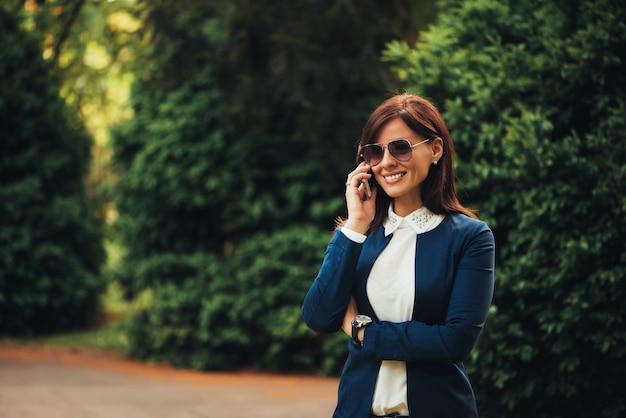 Frau, die auf dem mobile bei der erforschung des stadtparks spricht