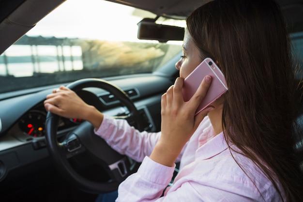 Frau, die auf dem mobiltelefon fährt das auto spricht