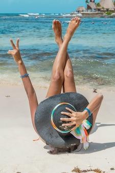 Frau, die auf dem sand liegt, der beine und arme ausbreitet. erholungsort riviera maya, quintana roo, mexiko