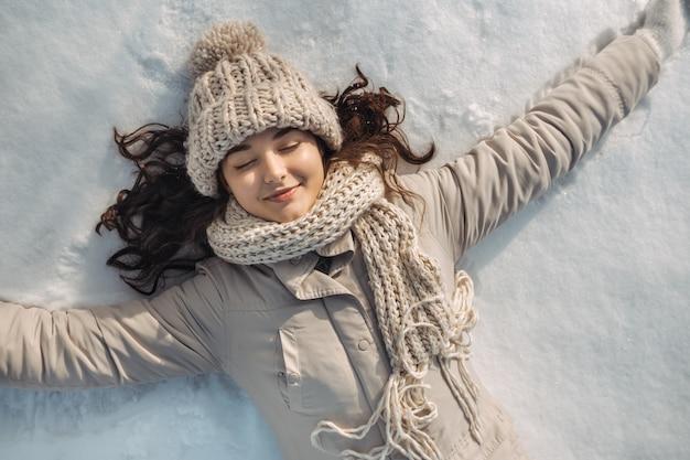 Frau, die auf dem schnee liegt