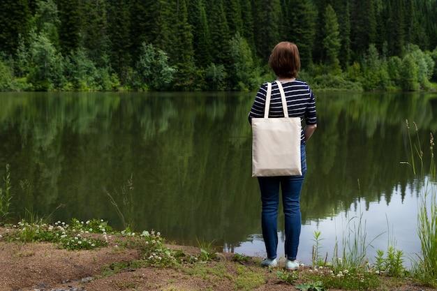 Frau, die auf dem seeufer steht, der leeres wiederverwendbares einkaufstaschenmodell trägt