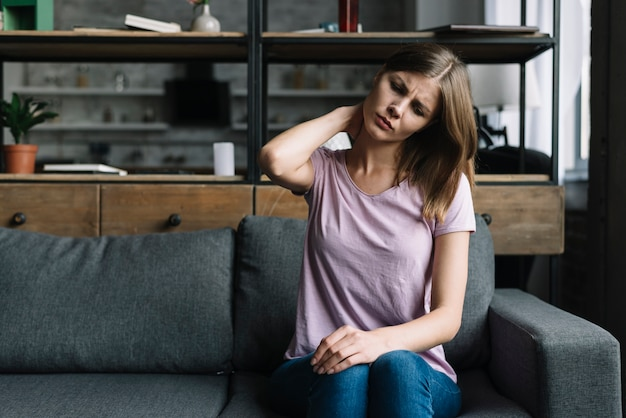 Frau, die auf dem sofa leiden unter nackenschmerzen sitzt
