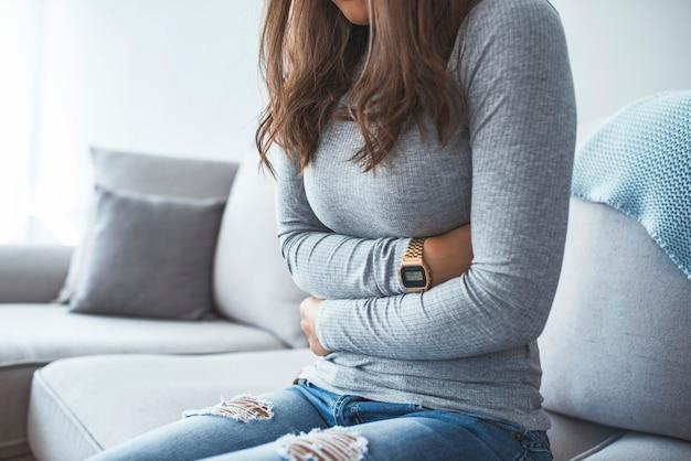 Frau, die auf dem sofa schaut krank im wohnzimmer liegt