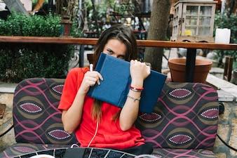 Frau, die auf dem Sofa sich versteckt hinter einem offenen Buch sitzt