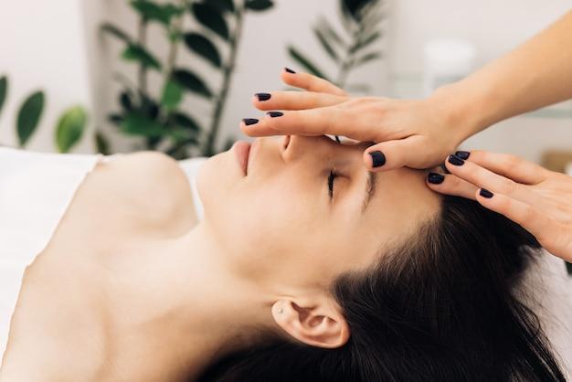 Frau, die auf dem spa-bett liegt, bekommt eine gesichtsmassage mit ätherischem aromaöl-hautpflege von massage