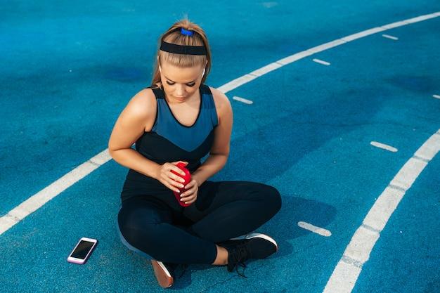Frau, die auf dem spielplatz mit einer flasche wasser sitzt