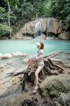 Frau, die auf dem stein am erawan-wasserfall am nationalpark kanchanaburi thailand sitzt