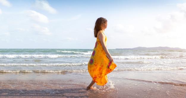 Frau, die auf dem strand im sommer mit hausgemachtem stoff geht