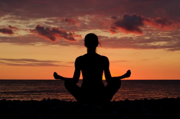 Frau, die auf dem strand in lotussitz meditiert. silhouette, sonnenuntergang