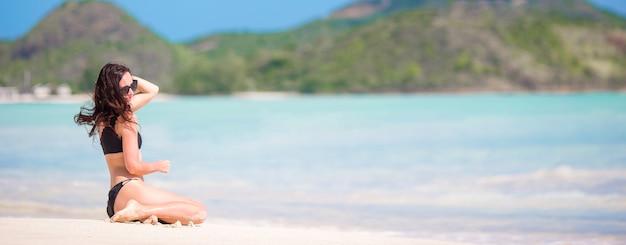 Frau, die auf dem strand lacht und die sommerferien betrachtet die kamera, schönes modell im bikini sich hinsetzt genießt sitzt.