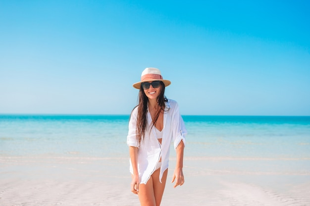 Frau, die auf dem strand liegt, der sommerferien betrachtet, das meer betrachtet