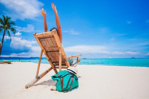 Frau, die auf dem strand liegt, der sommerferien betrachtet, die das meer betrachten