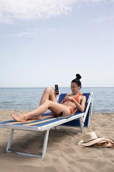 Frau, die auf dem strandstuhl betrachtet das telefon sitzt