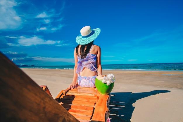 Frau, die auf dem stuhl nahe dem blauen meer sitzt und kokosnusssaft auf dem strand auf ho trinkt