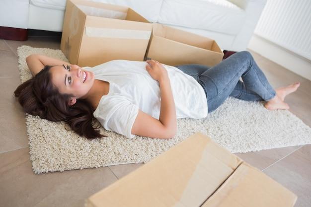 Frau, die auf dem teppich umgeben durch bewegliche kästen liegt