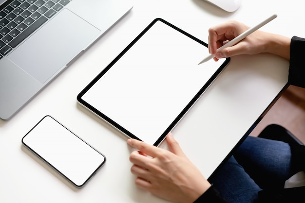 Frau, die auf dem tisch tablette, laptop und smartphone verwendet, verspotten oben des leeren bildschirms.
