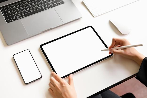 Frau, die auf dem tisch tablette, smartphoneschirmfreien raum und laptop verwendet