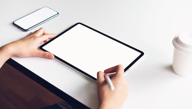 Frau, die auf dem tisch tablettenschirmfreien raum und smartphone verwendet