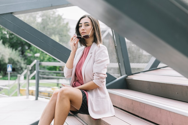 Frau, die auf dem treppenhaus entfernt sonnenbrillen sitzt