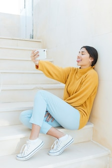 Frau, die auf dem treppenhaus nimmt das selfie macht lustiges gesicht sitzt