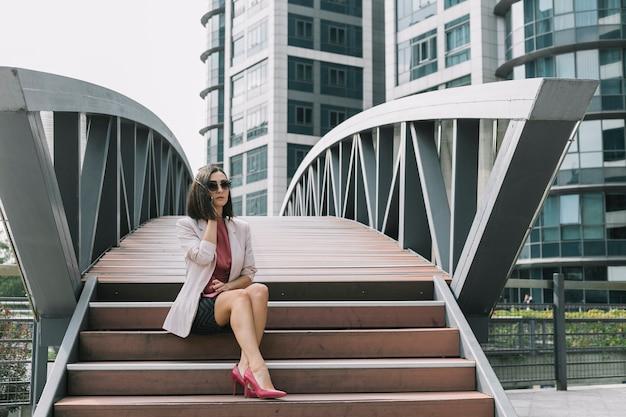 Frau, die auf dem treppenhaus spricht auf mobiltelefon sitzt