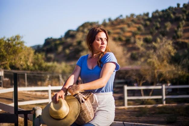 Frau, die auf dem zaun hält korb und hut auf dem gebiet sitzt