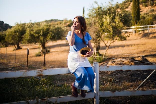 Frau, die auf dem zaun isst beeren in der schüssel sitzt
