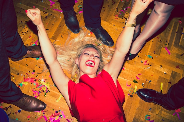 Frau, die auf den boden der disco legt und lacht