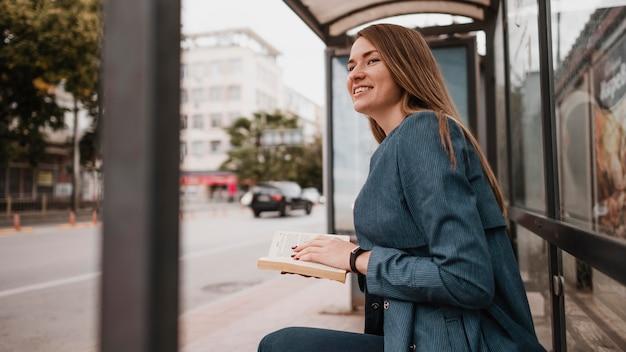 Frau, die auf den bus wartet und ein buch hält