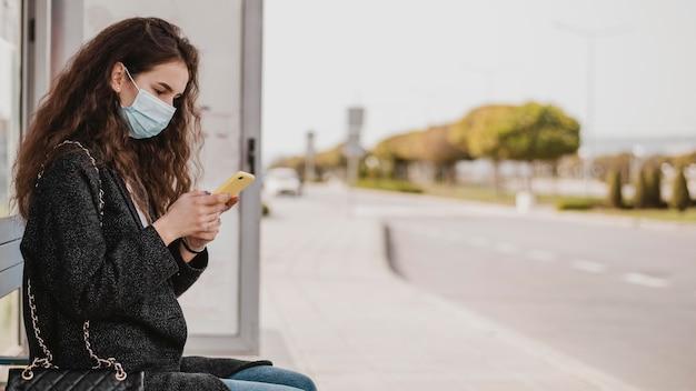 Frau, die auf den bus wartet und medizinische maske trägt