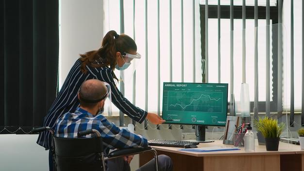 Frau, die auf den desktop zeigt und mit behinderten kollegen im neuen normalen büro vor dem computer spricht. team von finanzexperten, die an der computeranalyse von wirtschaftsdiagrammen unter berücksichtigung der sozialen distanz arbeiten.